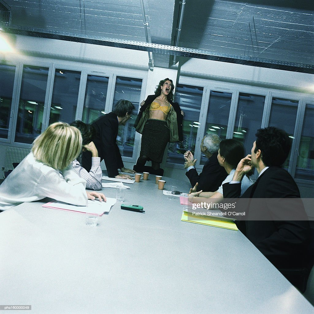 Young woman office worker standing on chair, stripping, colleagues watching. : Stockfoto