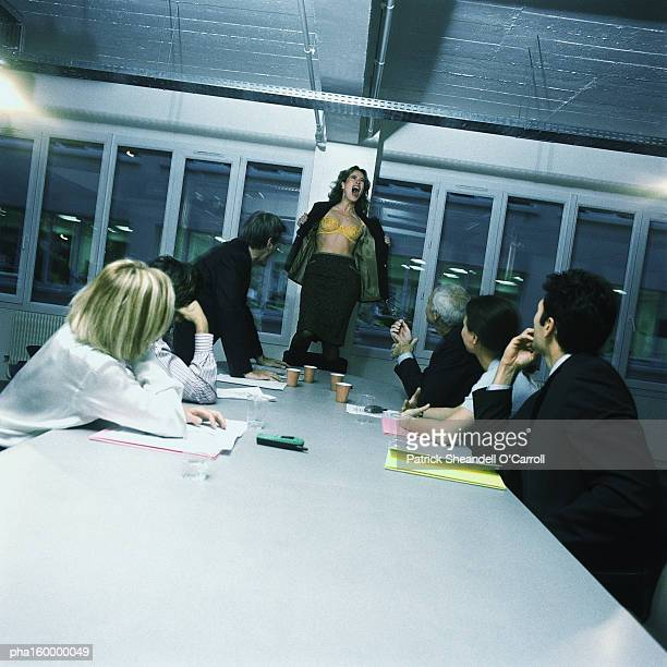 Young woman office worker standing on chair, stripping, colleagues watching.