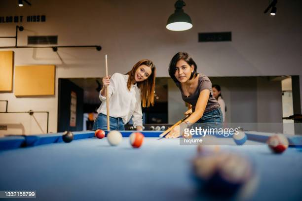 young woman office workers playing pool in the office - friendly match stock pictures, royalty-free photos & images