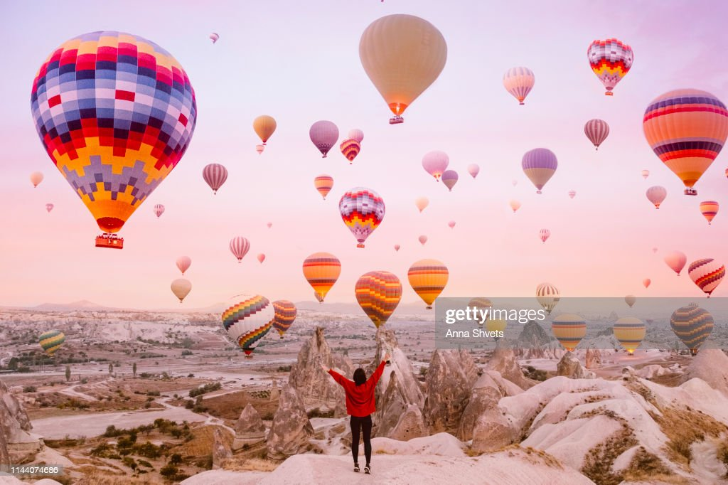 Young woman on a background of flying balloons at sunrise in Cappadocia : Stock Photo