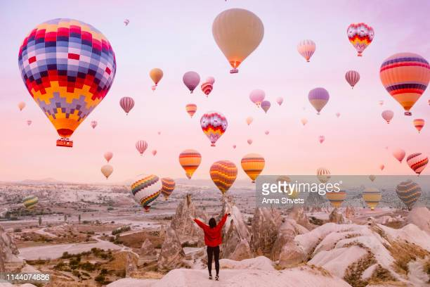 young woman on a background of flying balloons at sunrise in cappadocia - balloon ride stock pictures, royalty-free photos & images