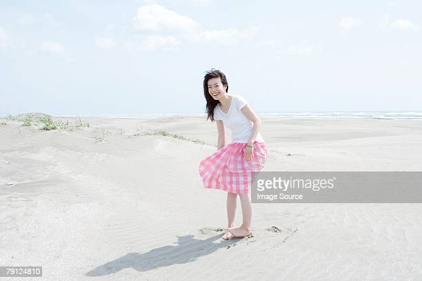 young woman on a beach - windy skirt stock photos and pictures