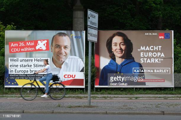 A young woman on a bicycle rides past election campaign billboards for Manfred Weber lead candidate of the German and Bavarian Christian Democrats...