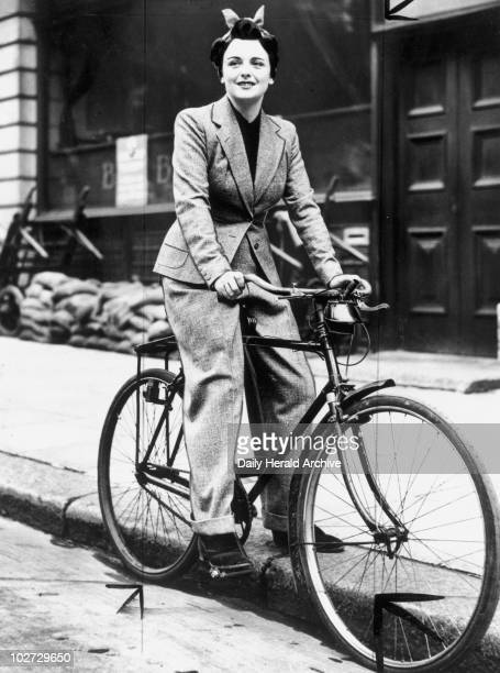 Young woman on a bicycle, wearing a trouser Young woman on a bicycle, wearing a trouser suit, 27 October 1939. 'Three-piece suit for wartime cycling...