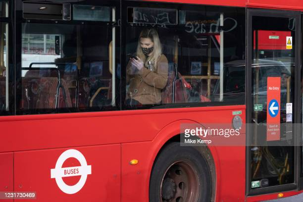Young woman on a bus looks closely at her smart phone as the national coronavirus lockdown three continues on 5th March 2021 in London, United...