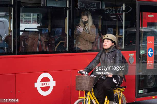 Young woman on a bus looks closely at her smart phone while a cyclist passes by outside as the national coronavirus lockdown three continues on 5th...