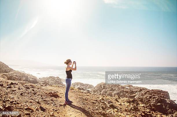 Young woman on a cliff, taking images of sea