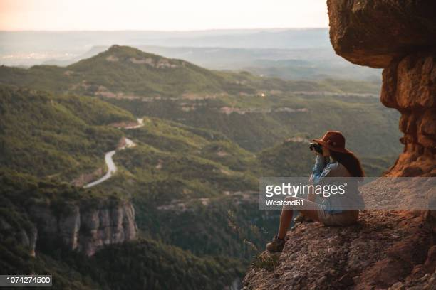 young woman on a hiking trip wearing a hat sitting on a rock taking a picture - actividad de fin de semana fotografías e imágenes de stock
