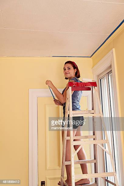 Young woman on a ladder getting room ready to re-paint.