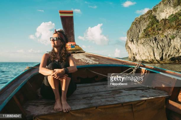 junge frau auf einem longtail-boot in thailand bei sonnenuntergang, phi phi island - asiatisches langboot stock-fotos und bilder