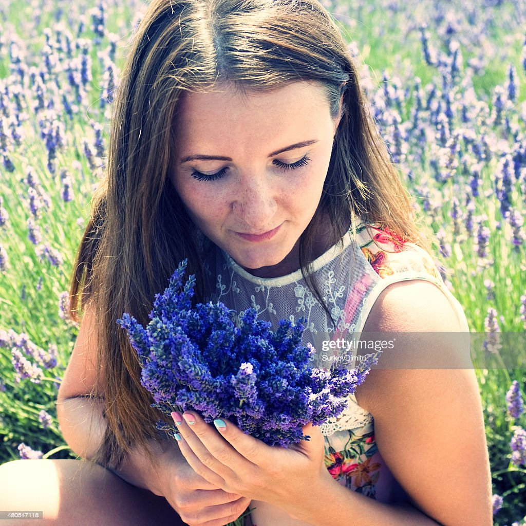 Young woman on a meadow with lavender flowers : Stock Photo