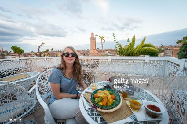 young woman on a roof terrace in the restaurant, moroccan food, tagine, view of the old town, mosque with minaret, evening mood, marrakech, morocco - tajine fotografías e imágenes de stock