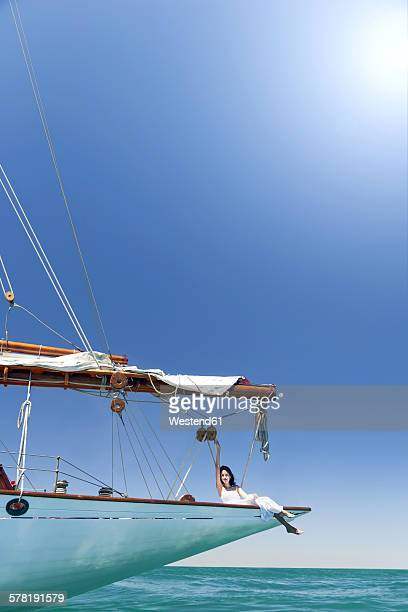 Young woman on a sailing trip sitting on bow