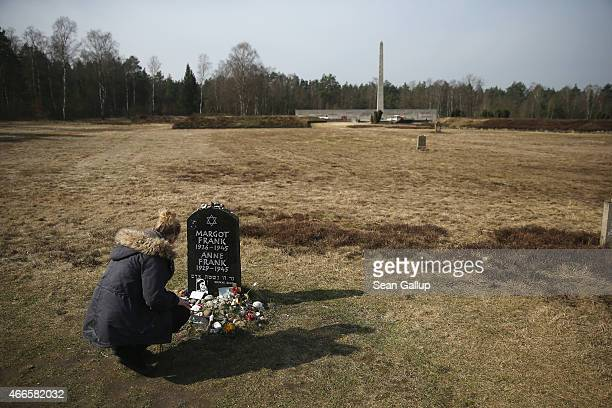 A young woman on a school excursion kneels at a tombstone that commemorates Anne Frank and her sister Margot on the site of the former BergenBelsen...