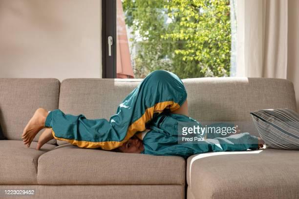 young woman on a sofa - trainingsanzug stock-fotos und bilder