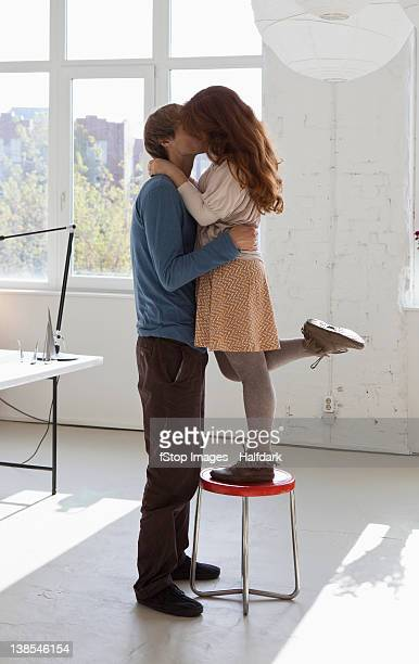 A young woman on a stool kissing her tall boyfriend