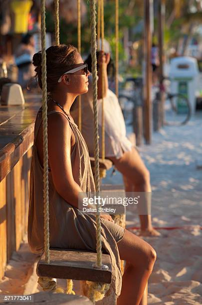young woman on a swing, enjoying the beach sunset - mujeres fotos stockfoto's en -beelden