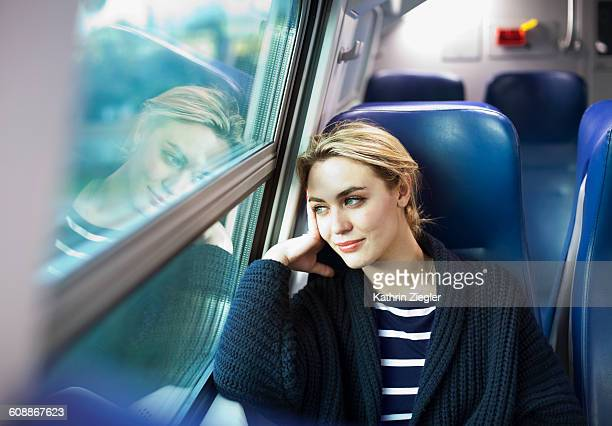 young woman on a train looking out the window