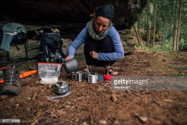 young woman on a trekking tour preparing drinks - überleben stock-fotos und bilder
