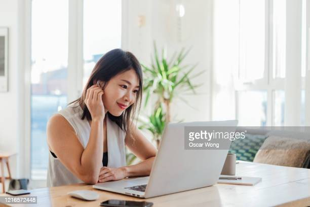 young woman on a video conference using laptop at home -  eラーニング ストックフォトと画像