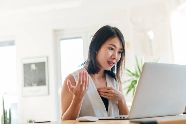 young woman on a video conference using laptop at home - asian woman using a laptop stock pictures, royalty-free photos & images