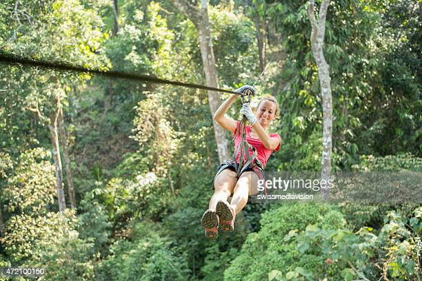 Jeune femme sur une tyrolienne traverser la forêt.