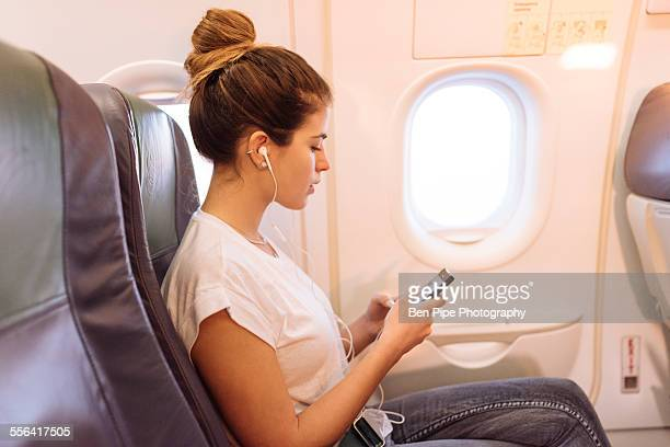 Young woman on airplane choosing music on smartphone
