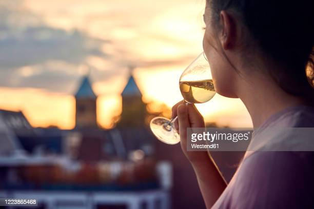 young woman on balcony drinking glass of white wine at sunset - golden hour stock pictures, royalty-free photos & images