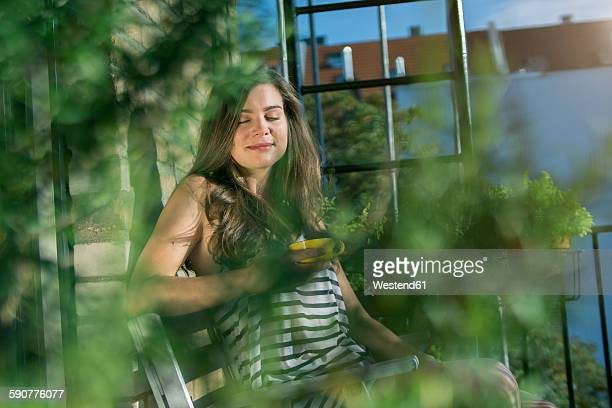 Young woman on balcony drinking morning coffee