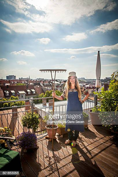 Young Woman On Balcony Holding Garden Rake, Munich, Bavaria, Germany, Europe