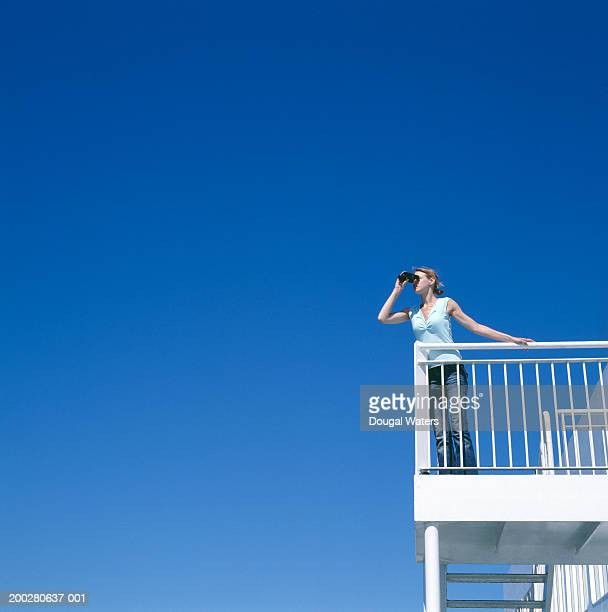 Young woman on balcony, looking through binoculars, low angle view