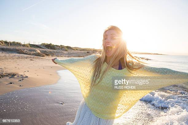 Young woman on beach, dancing, smiling