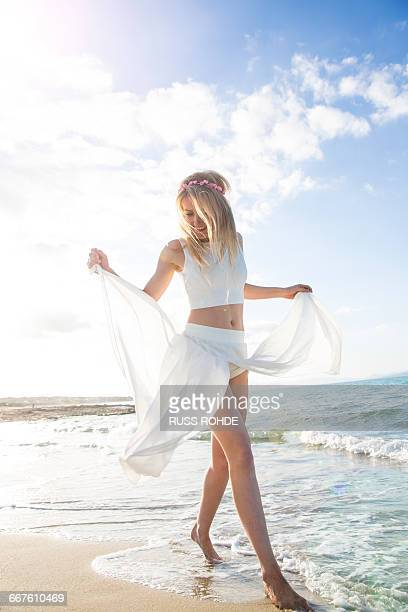 young woman on beach, dancing, smiling - crop top stock pictures, royalty-free photos & images