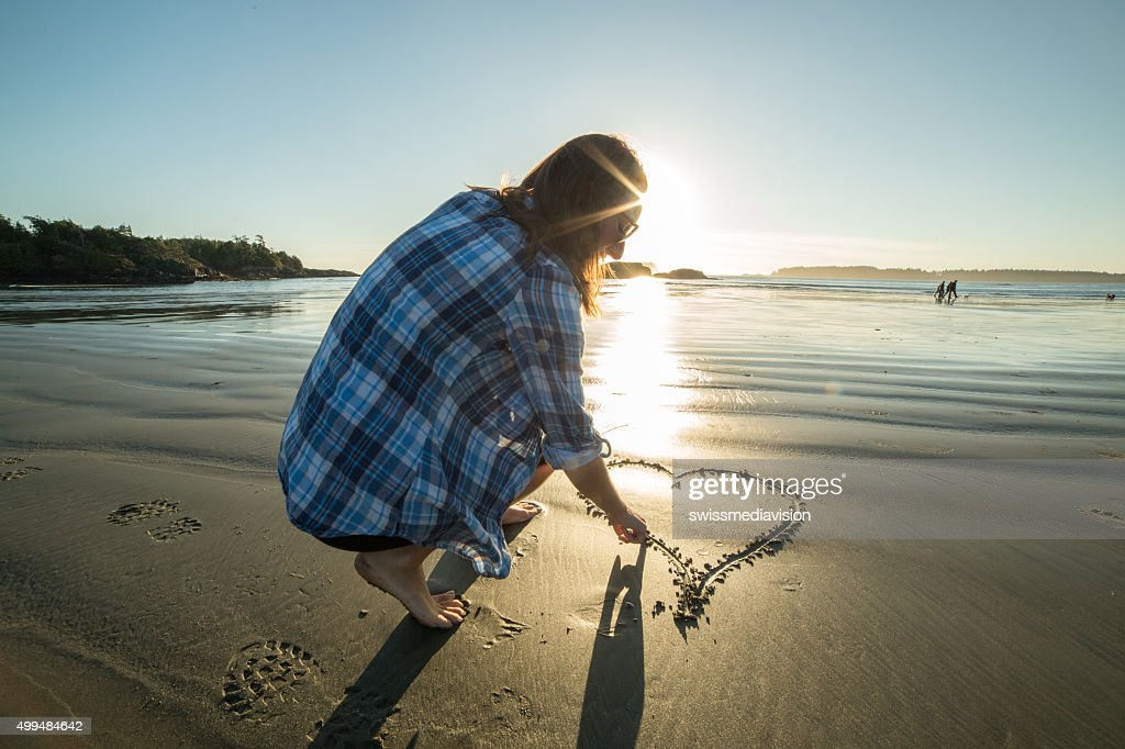 Young woman on beach drawing heart shape on sand-sunset : Stock Photo