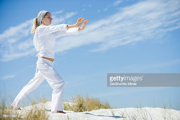 Young woman on beach, exercising