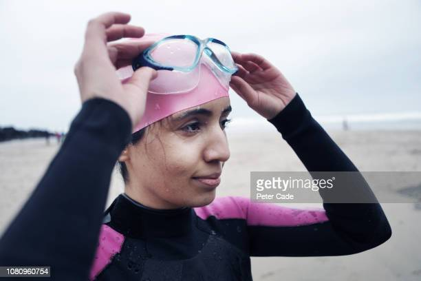 Young woman on beach in winter ready to swim