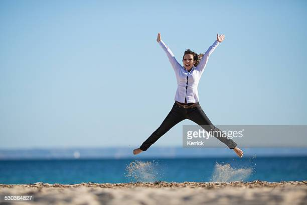 young woman on beach jumping with arms up