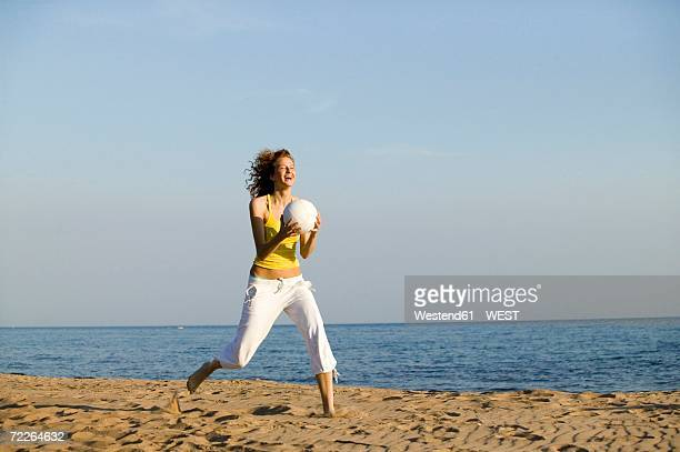 Young woman running on beach, holding ball, laughing
