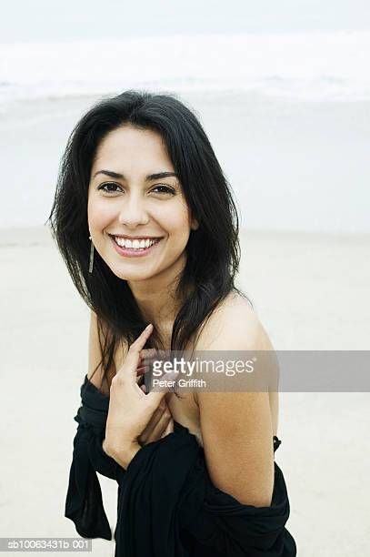 Young woman on beach, smiling, portrait