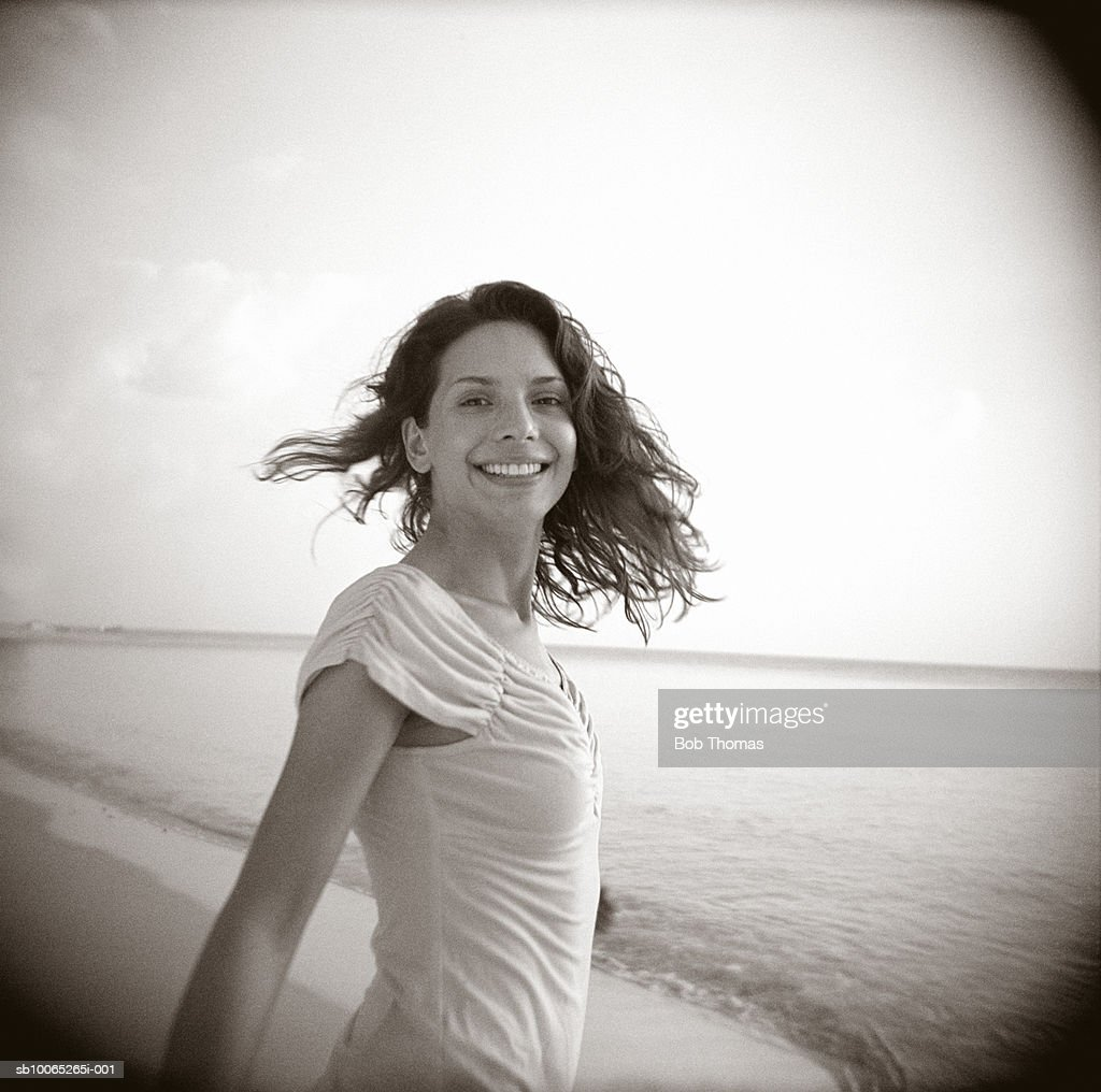 Young woman on beach, smiling, portrait (B&W) : Foto stock