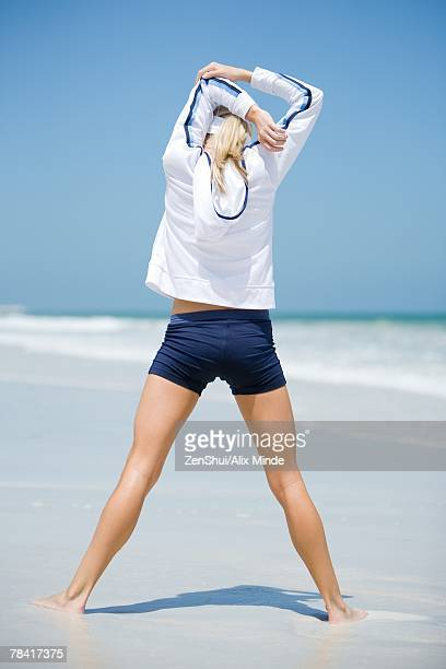 young woman on beach, stretching, rear view - legs spread woman stock photos and pictures