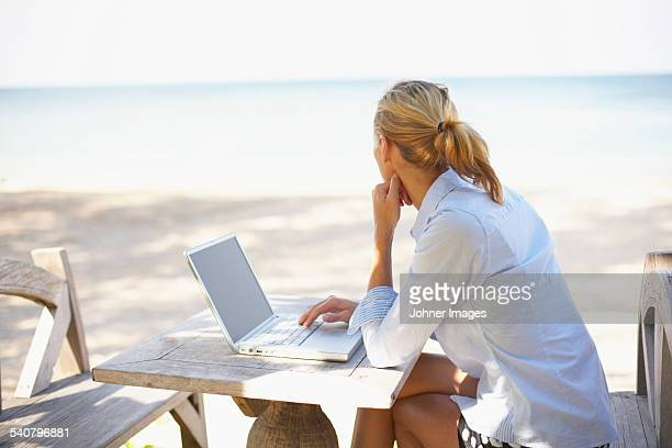 Young woman on beach using laptop