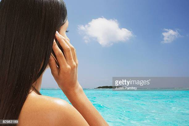 Young woman on beach using mobile phone
