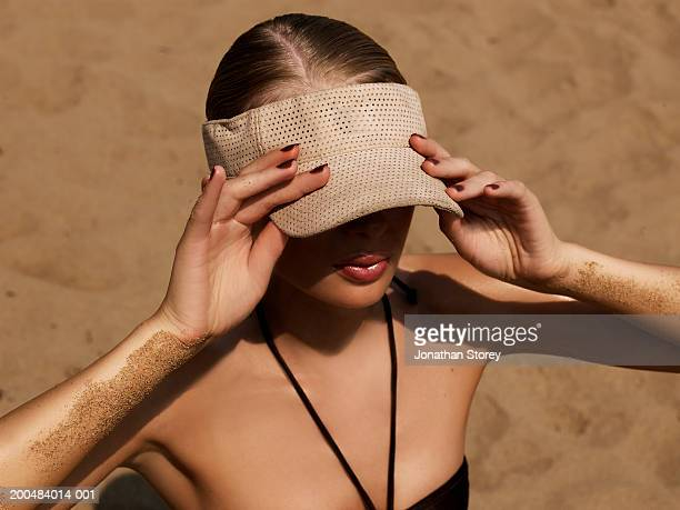 young woman on beach, wearing sun visor, elevated view - sunbathing stock pictures, royalty-free photos & images