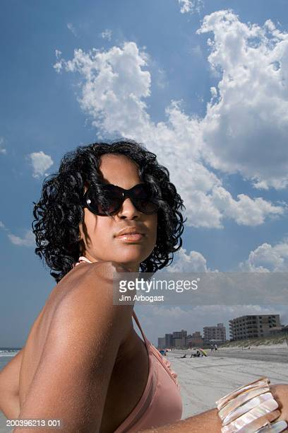Young woman on beach, wearing sunglasses, low angle view