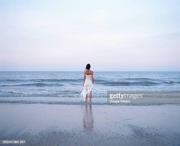 young woman on beach wearing white dress, facing ocean, rear view - vestido branco - fotografias e filmes do acervo