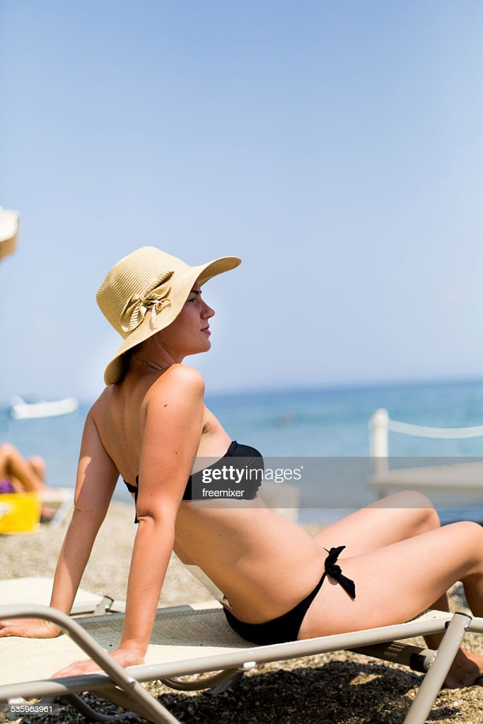 Young woman on beach with protectiv patch on back : Stock Photo