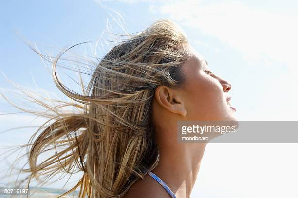 Young woman on beach with wind-swept hair close up side view head shot