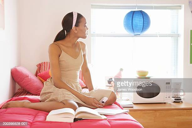 Young woman on bed looking out window in dorm room