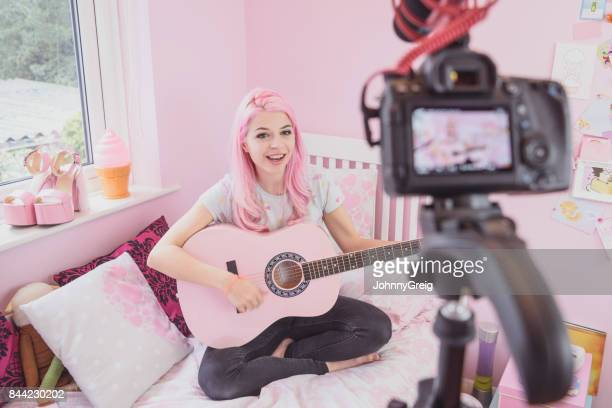 Young woman on bed playing guitar and filming herself on video blog